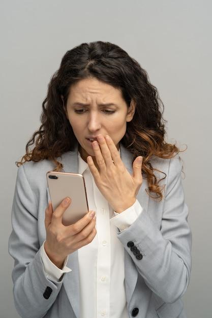 Gefrustreerde geschokte zakenvrouw of kantoormedewerker kijken naar telefoon verbluft met slecht negatief nieuws Premium Foto