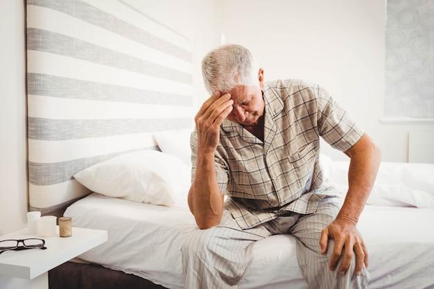 Gefrustreerde hogere mensenzitting op bed in slaapkamer Premium Foto