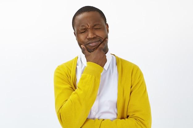 Gefrustreerde jonge bezorgd afro-amerikaanse man die hand op zijn kin houdt en vreselijke kiespijn ervaart, ogen sluit, pijnlijke lijdende blik heeft. mensen, levensstijl, gezondheid, ziekte en pijn Gratis Foto