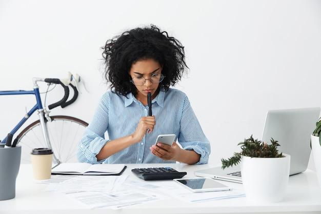 Gefrustreerde jonge vrouwelijke ondernemer in formele overhemd en brillen die een probleem hebben Gratis Foto