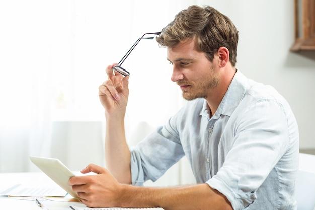 Gefrustreerde mens die digitale tablet in bureau gebruiken Premium Foto