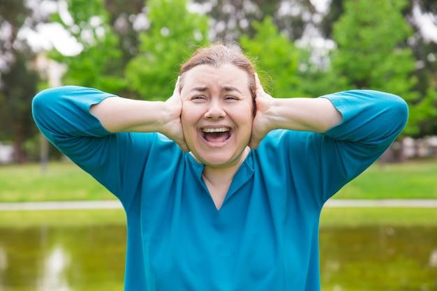Gefrustreerde ongelukkige vrouw die aan harde geluiden lijdt Gratis Foto