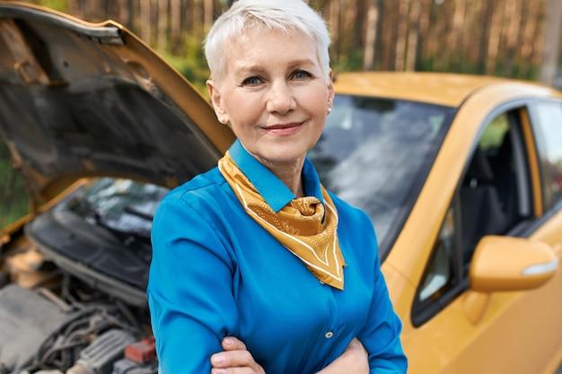 Gefrustreerde ongelukkige vrouwelijke gepensioneerde die bij haar auto staat met open kap, armen gekruist, wachtend op pechverhelping. Gratis Foto