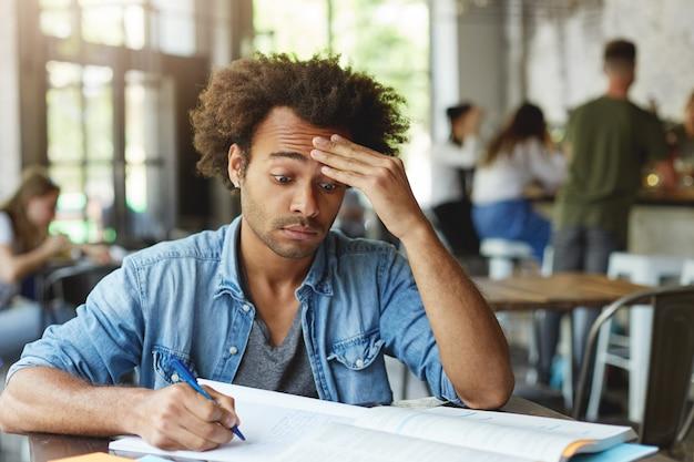 Gefrustreerde verwarde jonge student met afro-kapsel die voorhoofd wrijft, hard probeert ingewikkelde wiskundige problemen te begrijpen terwijl hij huiswerk maakt in café, pen gebruikt om aantekeningen te maken Gratis Foto