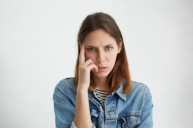 Gefrustreerde vrouw houdt vinger op tempel, probeert zich te concentreren op haar werk, maar voelt zich vermoeid, kijkt met vermoeide uitgeputte uitdrukking Gratis Foto