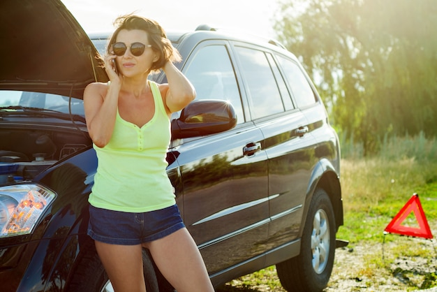 Gefrustreerde vrouwenbestuurder dichtbij gebroken auto Premium Foto