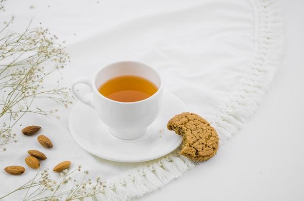 Gegeten koekjes en amandelen met witte kruidentheekop op tafelkleed Gratis Foto
