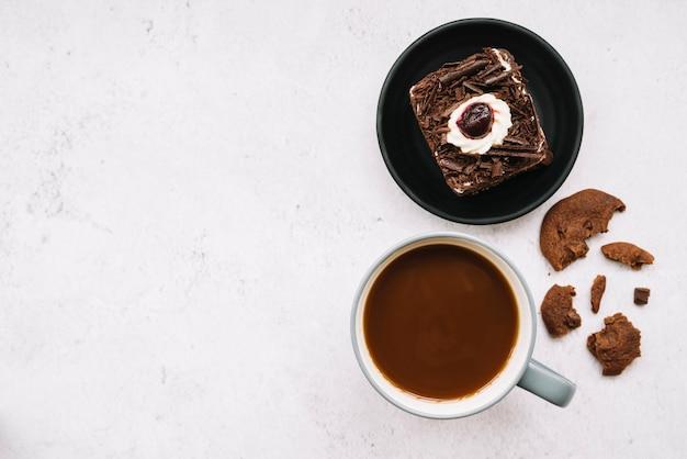 Gegeten koekjes; plakje cake en koffiekopje op witte achtergrond Gratis Foto