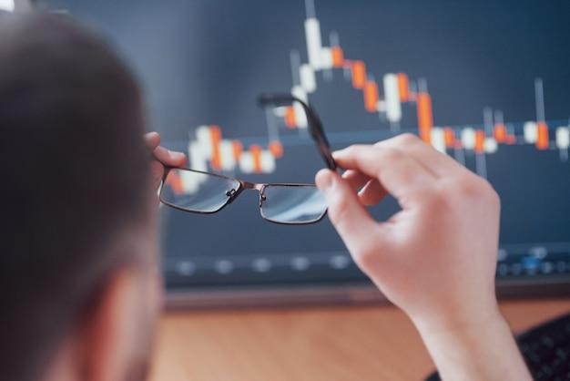 Gegevens analyseren. sluit omhoog van een jonge zakenman die glazen houdt en gff bekijkt terwijl het werken in een creatief bureau Gratis Foto