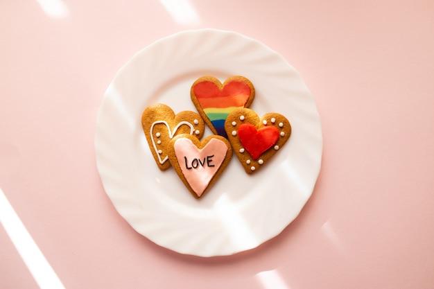 Geglazuurde hartvormige koekjes. lgbt en liefdes-tekst. bakken met liefde voor valentijnsdag, liefde en diversiteitsconcept. Premium Foto
