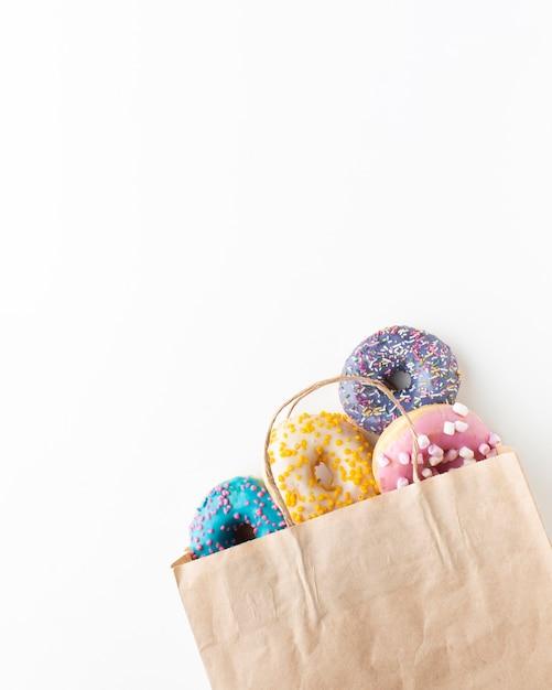 Geglazuurde kleurrijke donuts in papieren zak Gratis Foto