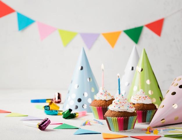 Geglazuurde muffins met kaarsen en feestmutsen Gratis Foto