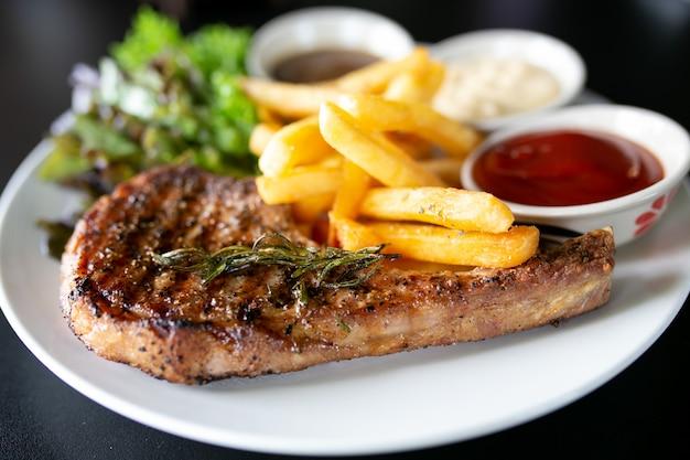 Gegrild vlees, porkchops steak met pepersaus en salade. Premium Foto
