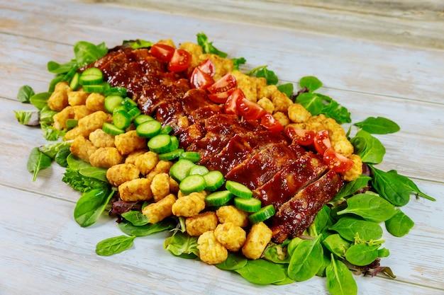Gegrilde bbq spareribs met groene salade en aardappel. Premium Foto