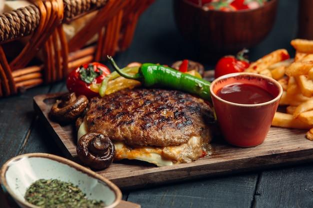 Gegrilde bbq steak sandwich met kaas en groenten samen met frietjes Gratis Foto