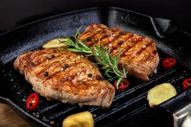 Gegrilde biefstuk in grillpan met rozemarijn, pepers en gember op houten bord. Premium Foto