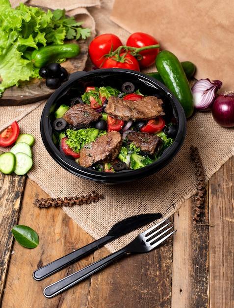 Gegrilde biefstukplakken met groene salade, tomaten en olijven Gratis Foto