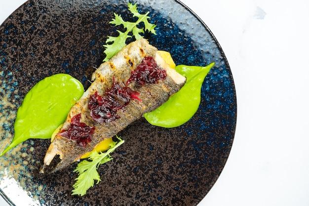 Gegrilde forel met gekarameliseerde bieten en groene puree op een zwarte plaat op een marmeren tafel. zeevruchten. maaltijd met vis. Premium Foto