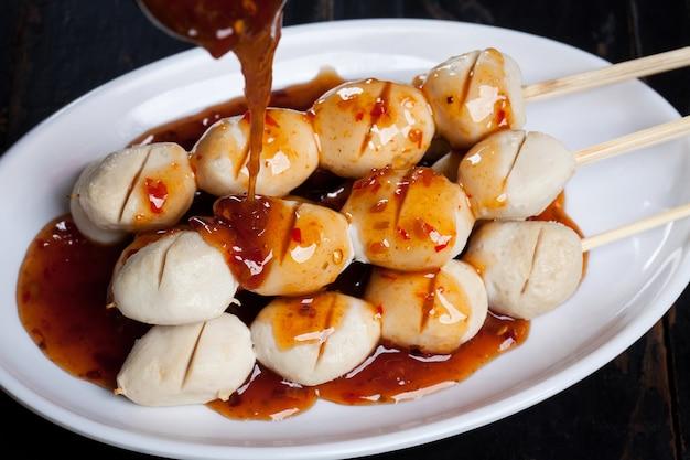 Gegrilde gehaktballetjes spies bamboe op een witte plaat met pittige saus op houten tafel Premium Foto