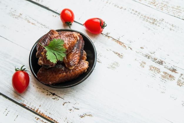 Gegrilde gezonde kip in kom met tomaat op houten bureau Gratis Foto