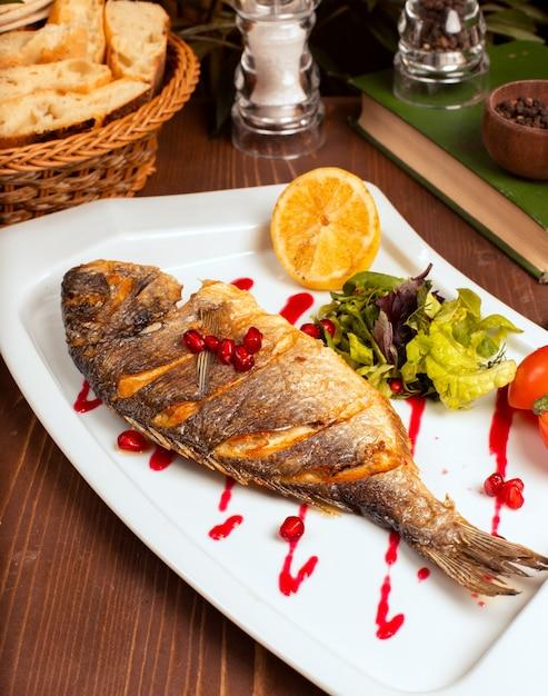 Gegrilde hele vis met gele saus, groentesalade, citroen en granaatappelzaden in witte plaat Gratis Foto