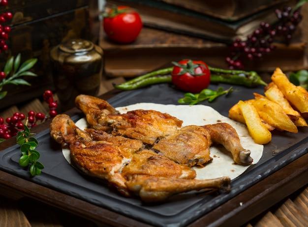 Gegrilde kip met geroosterde aardappelen in lavash op een stenen bord Gratis Foto