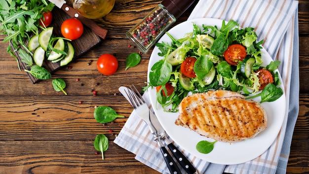 Gegrilde kipfilet en verse groentesalade - tomaten, komkommers en slabladeren. kip salade. gezond eten. plat leggen. bovenaanzicht Gratis Foto