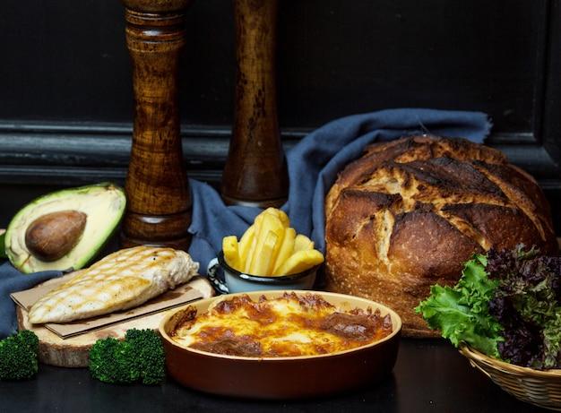 Gegrilde kipfilet geserveerd met friet, pan gesmolten kaas en broodbroodje Gratis Foto