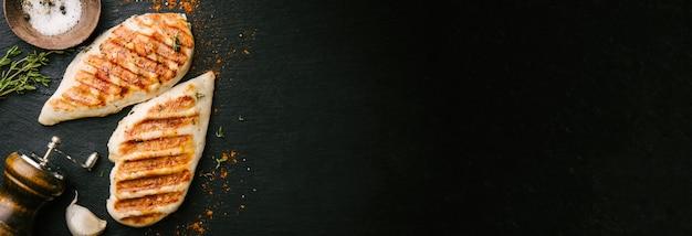 Gegrilde kippenborst geserveerd op zwarte leisteen Gratis Foto