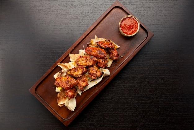 Gegrilde kippenvleugels in saus, met ketchup, op een houten bord, op een donkere achtergrond Premium Foto