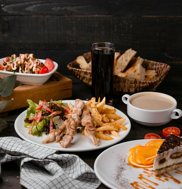 Gegrilde kipstengels met friet en salade Gratis Foto
