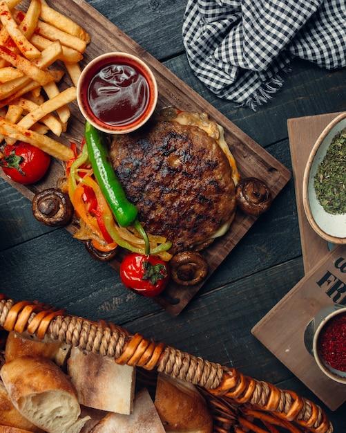 Gegrilde lamsvleesloze hamburger geserveerd met geroosterde paprika, friet, champignon, ketchup Gratis Foto