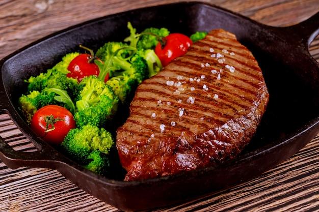 Gegrilde medium zeldzame biefstuk met broccoli en tomaat op de grillpan. Premium Foto