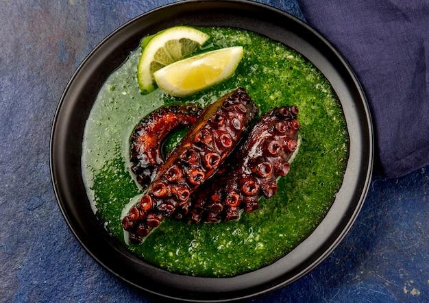 Gegrilde octopus serveert met grijnsaus op zwarte plaat Premium Foto