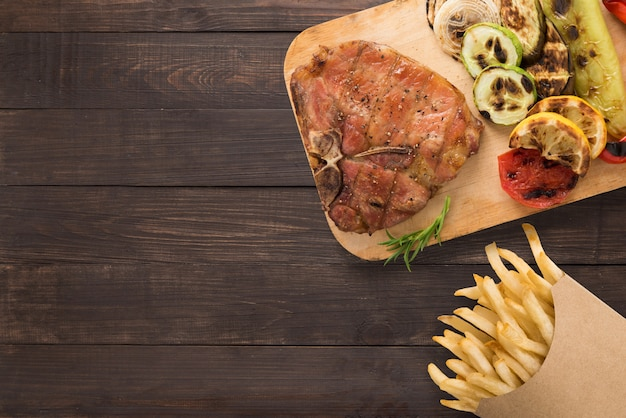 Gegrilde varkenskotelet en chips op de houten achtergrond. copyspace voor uw tekst Premium Foto