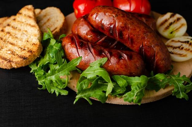 Gegrilde varkensworst met rucola en groenten op zwarte achtergrond. . Premium Foto