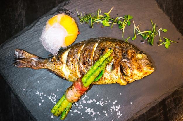 Gegrilde vis close-up versierd met groenten Gratis Foto