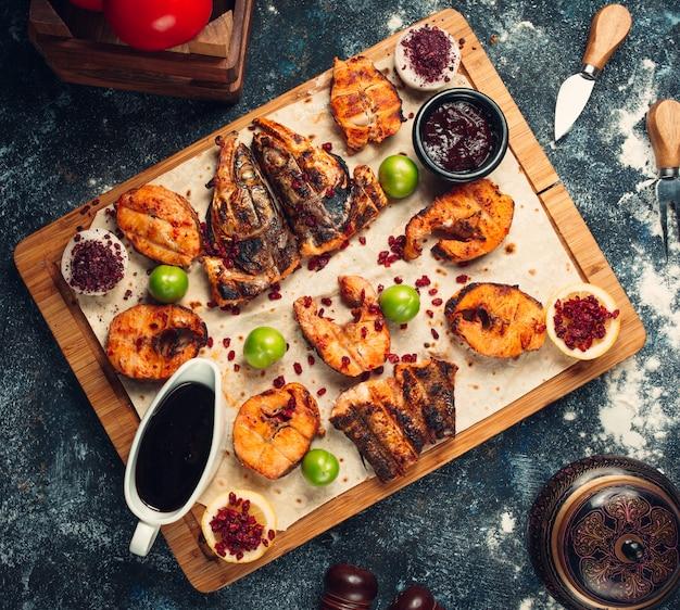 Gegrilde vis in stukjes gesneden geserveerd op flatbread met sauzen, sumak Gratis Foto