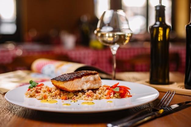 Gegrilde visfilet geserveerd bovenop de couscous salade met paprika Gratis Foto