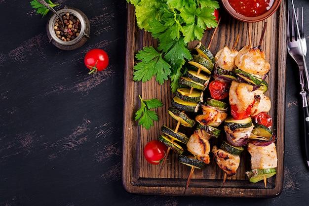 Gegrilde vleesspiesen, kip shish kebab met courgette, tomaten en rode uien Premium Foto