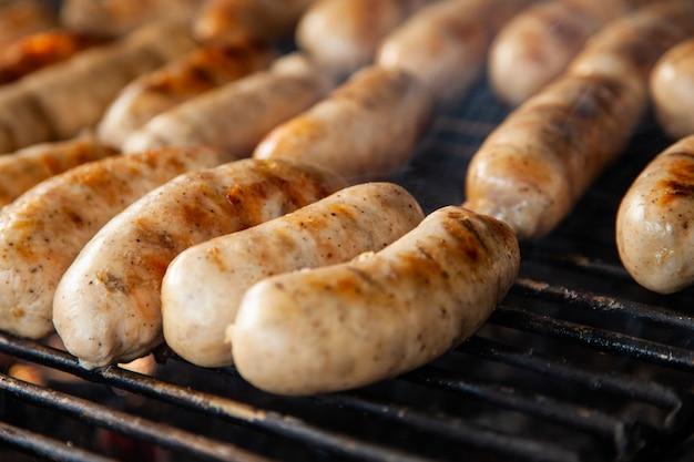 Gegrilde vleesworsten op houtskoolgrill Premium Foto