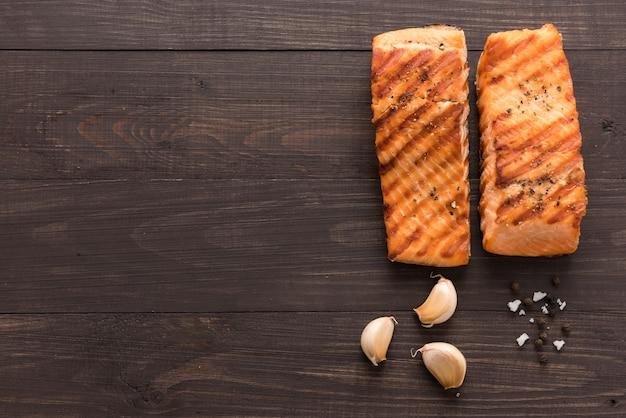 Gegrilde zalm met knoflook, peper, zout op houten achtergrond. Premium Foto