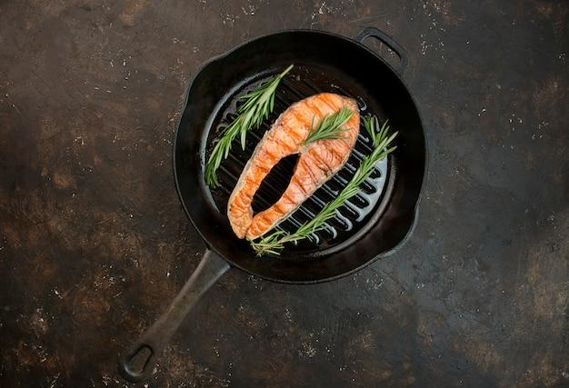 Gegrilde zalmfiletbiefstuk met aromatische kruiden, specerijen en groenten in een grillpan. seafood. koken concept. culinaire achtergrond. tabel achtergrond menu. kopieer ruimte Premium Foto