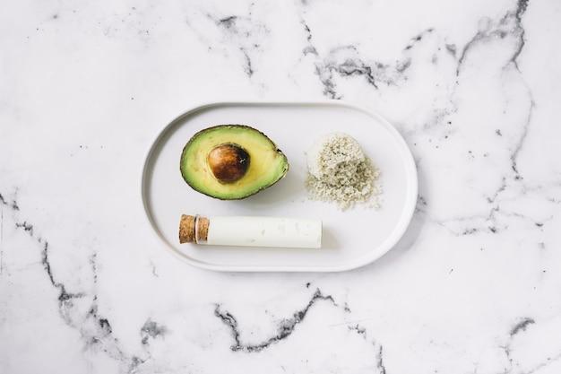 Gehalveerde avocado; geraspte lichaamsboen en reageerbuis op wit dienblad tegen marmeren geweven achtergrond Gratis Foto
