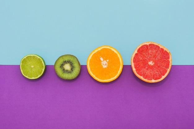Gehalveerde citroen; kiwi; sinaasappel en druiven fruit op dubbele achtergrond Gratis Foto