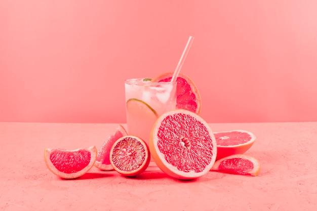 Gehalveerde grapefruits en glas sap op koraalachtergrond Premium Foto