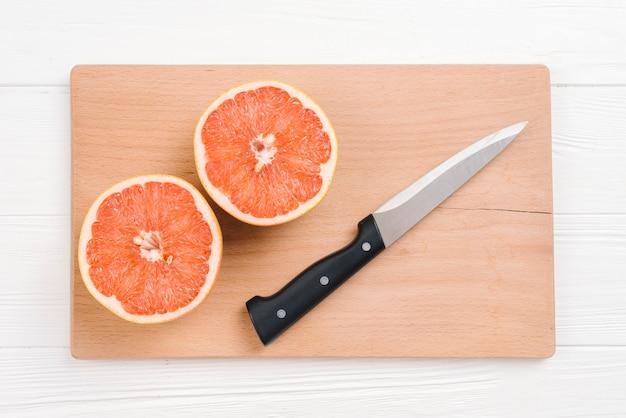 Gehalveerde grapefruits met scherp mes op houten hakbord over wit bureau Gratis Foto