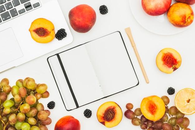 Gehalveerde perzik; druiven en braambessen op laptop; dagboek en pen op witte achtergrond Gratis Foto