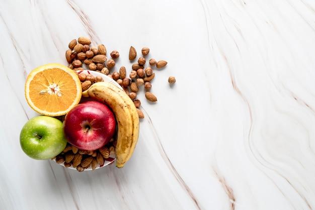 Gehalveerde sinaasappel; appel; banaan met amandel en hazelnoot op kom Gratis Foto