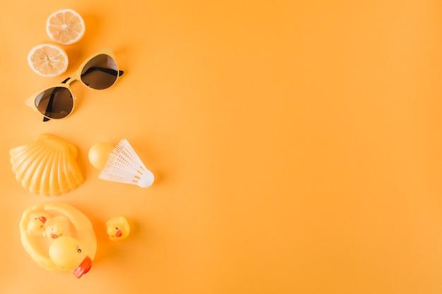 Gehalveerde sinaasappelen; zonnebril; plastic bal; shuttle; coquille en rubberen eend op gekleurde achtergrond Gratis Foto